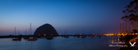 Morro Bay Harbor with Morro Rock on the horizon, just after the sun has gone down.